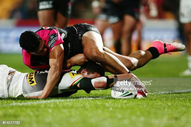 Nathan Cleary of the Panthers scores a try against Roger Tuivasa-Sheck of the Warriors during the round 19 NRL match between the New Zealand Warriors...
