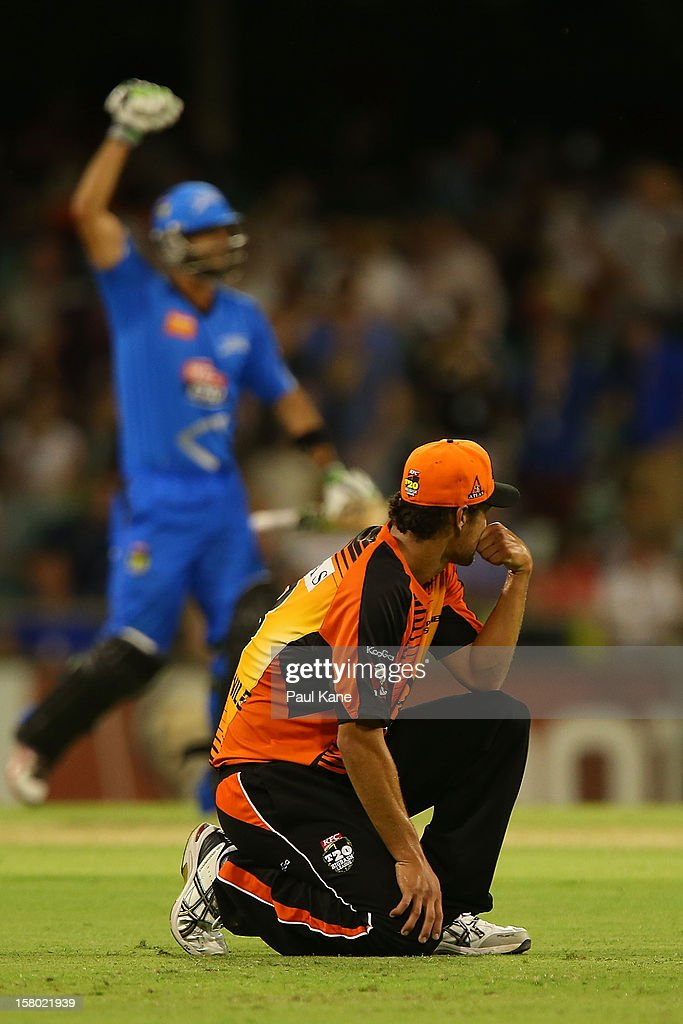Nathan Coulter-Nile of the Scorchers looks on as Theo Doropoulos of the Strikers celebrates winning the Big Bash League match between the Perth Scorchers and Adelaide Strikers at WACA on December 9, 2012 in Perth, Australia.