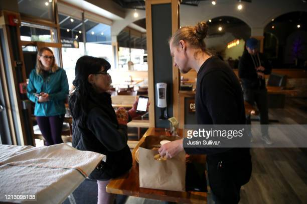 Nathan Crawford helps a customer with a to go order at Creekside Pizza and Taproom on March 17 2020 in San Anselmo California Restaurants are only...