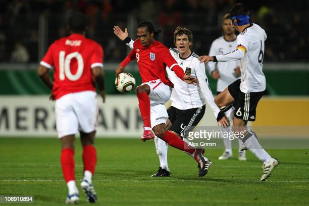 Nathan Delfouneso of England is challenged by Stefan Bell and Christoph Moritz of Germany during the U21 international friendly match between Germany...