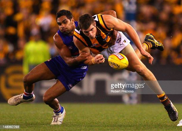 Nathan Djerrkura of the Bulldogs contests the ball with Ben Stratton of the Hawks during the round 16 AFL match between the Western Bulldogs and the...