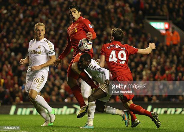 Nathan Dyer of Swansea City tangles with Jack Robinson and Luis Suarez of Liverpool during the Capital One Cup Fourth Round match between Liverpool...