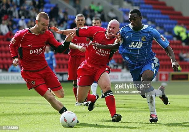 Nathan Ellington of Wigan battles with Robert Page and Rhys Weston of Cardiff to score the second goal during the CocaCola Championship match between...