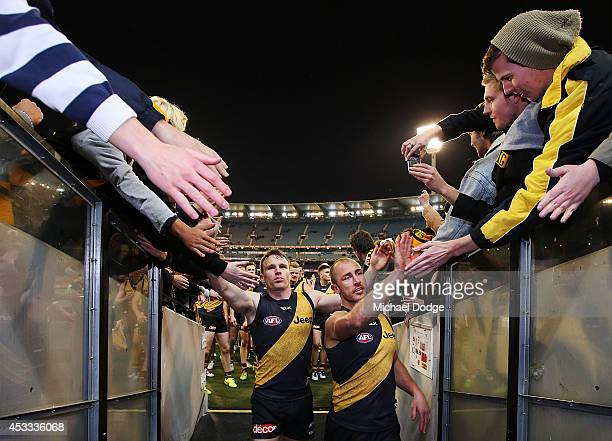Nathan Foley and Matt Thomas of the Tigers celebrate their woin with fans during the round 20 AFL match between the Richmond Tigers and the Essendon...