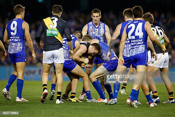 Nathan Foley of the Tigers is tackled during the round 12 AFL match between the North Melbourne Kangaroos and the Richmond Tigers at Etihad Stadium...
