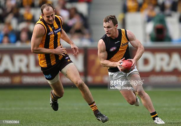 Nathan Foley of the Tigers runs with the ball away from David Hale of the Hawks during the round 19 AFL match between the Hawthorn Hawks and the...