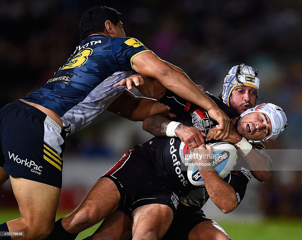 Nathan Friend of the Warriors is tackled by Johnathan Thurston and Jason Taumalolo of the Cowboys during the round seven NRL match between the North Queensland Cowboys and the New Zealand Warriors at 1300SMILES Stadium on April 18, 2015 in Townsville, Australia.
