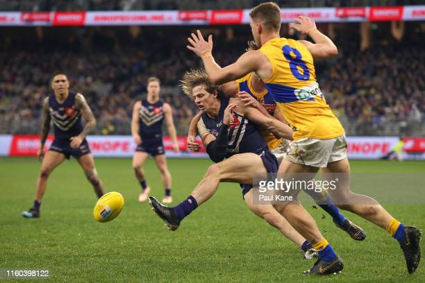 Nathan Fyfe of the Dockers gets his kick away under pressure during the round 16 AFL match between the Fremantle Dockers and the West Coast Eagles at...