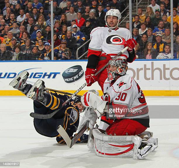 Nathan Gerbe of the Buffalo Sabres is upended by Jamie McBain of the Carolina Hurricanes in front of goaltender Cam Ward at First Niagara Center on...