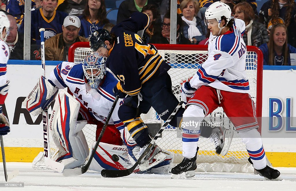 Nathan Gerbe #42 of the Buffalo Sabres jumps to avoid a shot in front of Henrik Lundqvist #30 and Michael Del Zotto #4 of the New York Rangers at First Niagara Center on April 19, 2013 in Buffalo, New York.