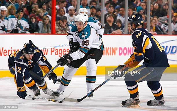 Nathan Gerbe of the Buffalo Sabres sweeps the puck away from Tomas Pihal of the San Jose Sharks as Tim Connolly of the Sabres watches on February 13...