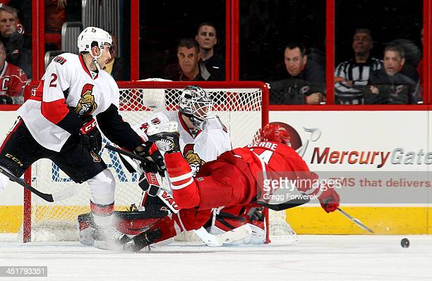 Nathan Gerbe of the Carolina Hurricanes dives in front of Jared Cowen and Robin Lehner of the Ottawa Senators in an attempt to collect a pass during...