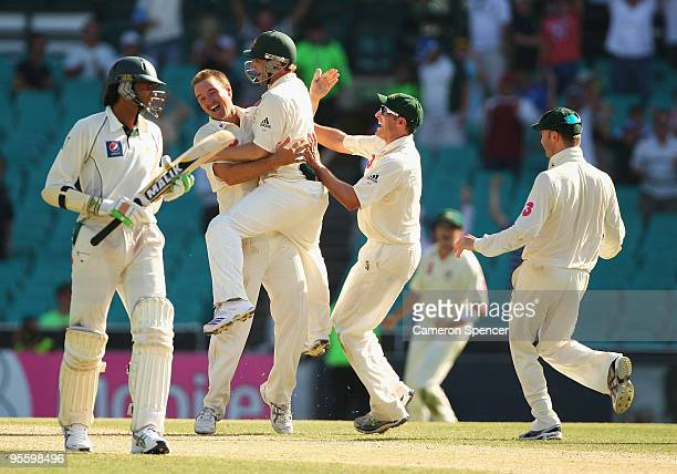 Nathan Hauritz of Australia celebrates with team mates after taking the final wicket of Umar Gul of Pakistan to win the test match during day four of...