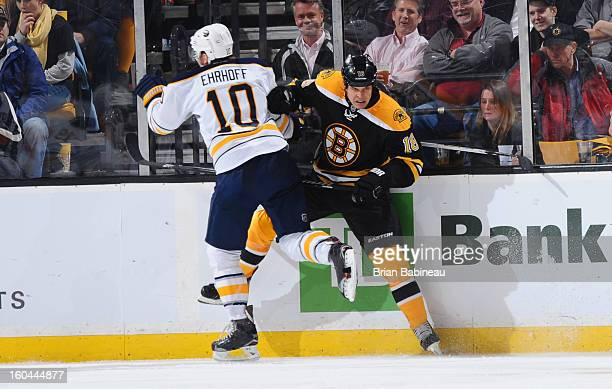 Nathan Horton of the Boston Bruins gets checked against by Christian Ehrhoff of the Buffalo Sabres at the TD Garden on January 31 2013 in Boston...