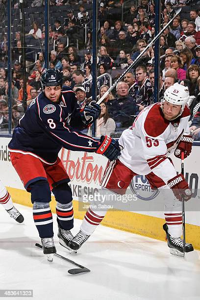 Nathan Horton of the Columbus Blue Jackets and Derek Morris of the Phoenix Coyotes battle for control of a loose puck on April 8, 2014 at Nationwide...