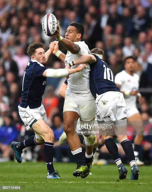 Nathan Hughes of England stretches to collect the ball while Finn Russell of Scotland takcles him during the RBS Six Nations match between England...