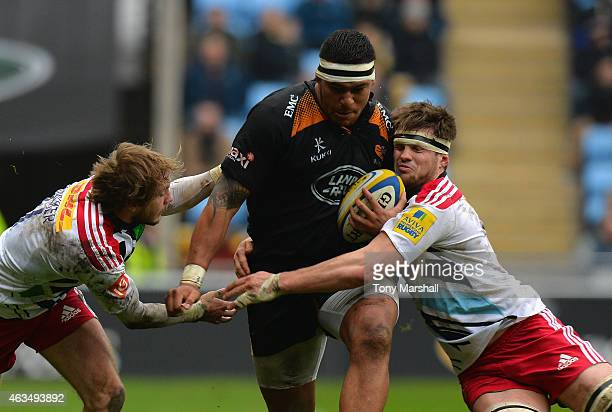 Nathan Hughes of Wasps is tackled by Charlie Walker and Jack Clifford of Harlequins during the Aviva Premiership match between Wasps and Harlequins...