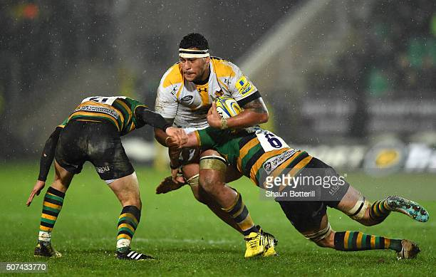 Nathan Hughes of Wasps is tackled by Lee Dickson of Northampton Saints and Tom Wood of Northampton Saints during the Aviva Premiership match between...