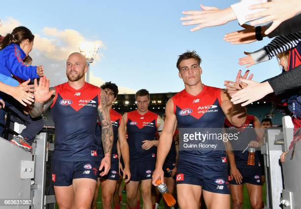 Nathan Jones and Jack Viney of the Demons high five fans after winning the round two AFL match between the Melbourne Demons and the Carlton Blues at...