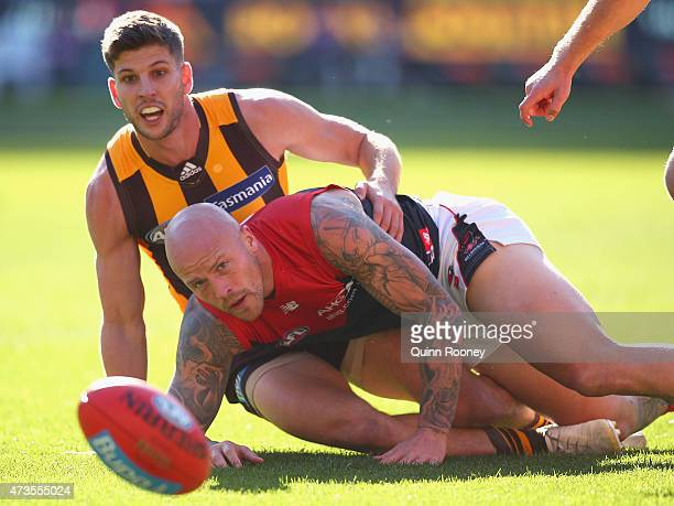 Nathan Jones of the Demons handballs whilst being tackled by Luke Breust of the Hawks during the round seven AFL match between the Hawthorn Hawks and...