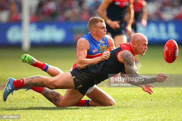 Nathan Jones of the Demons handballs whilst being tackled by Mitch Robinson of the Lions during the round 16 AFL match between the Melbourne Demons...