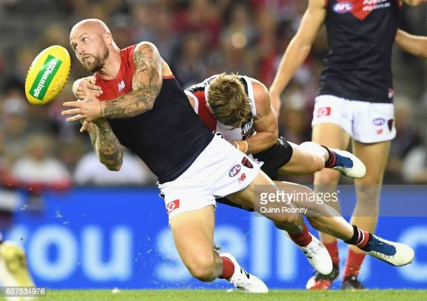 Nathan Jones of the Demons handballs whilst being tackled during the round one AFL match between the St Kilda Saints and the Melbourne Demons at...