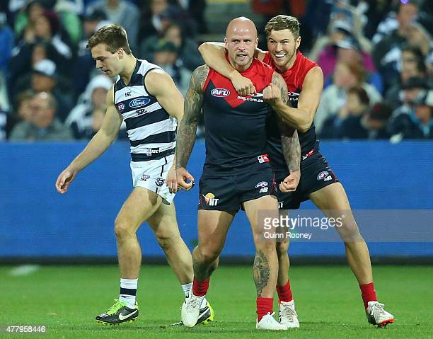 Nathan Jones of the Demons is congratulated by Rohan Bail after kicking a goal during the round 12 AFL match between the Geelong Cats and the...