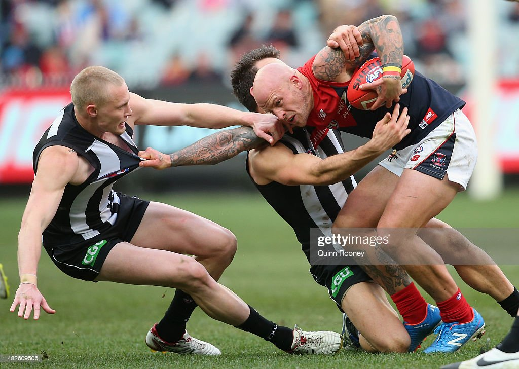 Nathan Jones of the Demons is tackled by Jack Frost and Levi Greenwood of the Magpies during the round 18 AFL match between the Collingwood Magpies and the Melbourne Demons at Melbourne Cricket Ground on August 1, 2015 in Melbourne, Australia.
