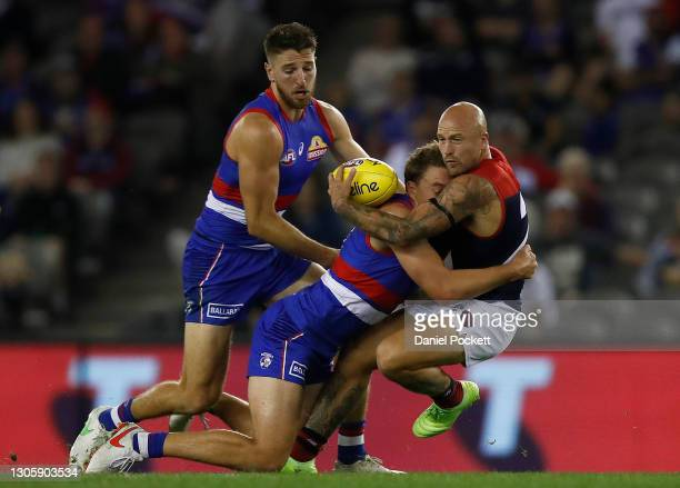 Nathan Jones of the Demons is tackled by Jack Macrae of the Bulldogs during the AFL Community Series match between the Western Bulldogs and the...