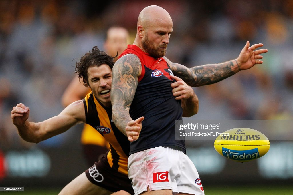 Nathan Jones of the Demons kicks the ball whilst being tackled by Isaac Smith of the Hawks during the round four AFL match between the Hawthorn Hawks and the Melbourne Demons at Melbourne Cricket Ground on April 15, 2018 in Melbourne, Australia.