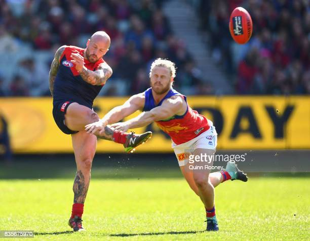 Nathan Jones of the Demons kicks whilst Daniel Rich of the Lions attempts to smouther during the round 22 AFL match between the Melbourne Demons and...