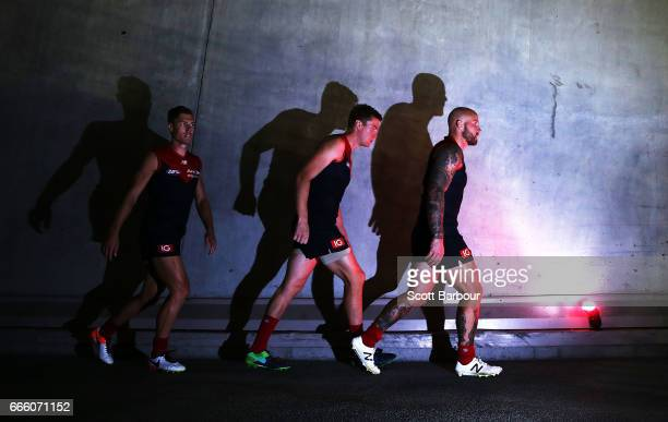 Nathan Jones of the Demons Tom McDonald of the Demons and Jake Melksham of the Demons leave their rooms and walk onto the field during the round...