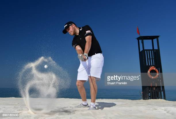 Nathan Kinsey of England plays a shot on the beach prior to the start of The Rocco Forte Open at Verdura Golf and Spa Resort on May 16 2017 in...