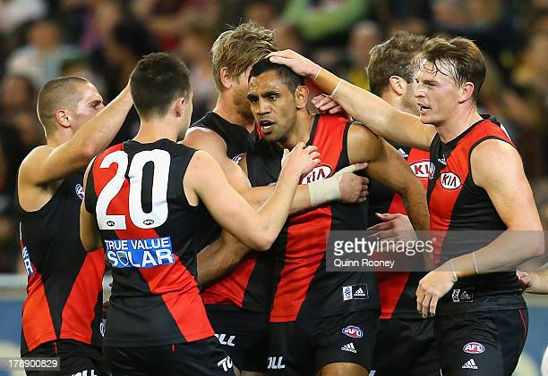 Nathan LovettMurray of the Bombers is congratulated by team mates after kicking a goal during the round 23 AFL match between the Essendon Bombers and...