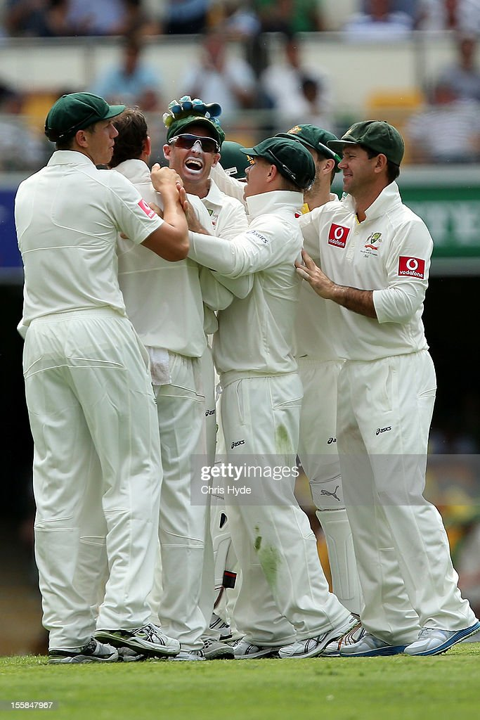Nathan Lyon and Michael Hussey of Australia celebrate combining to take the wicket of Alviro Petersen of South Africa during day one of the First Test match between Australia and South Africa at The Gabba on November 9, 2012 in Brisbane, Australia.