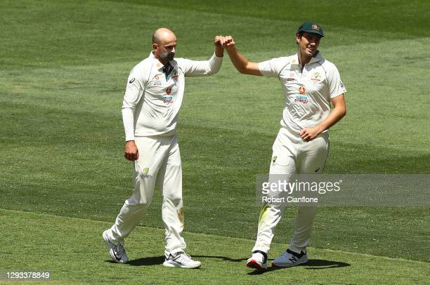 Nathan Lyon and Pat Cummins of Australia celebrates taking the wicket of Umesh Yadav of India during day three of the Second Test match between...