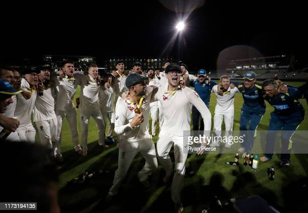 Nathan Lyon and Steve Smith of Australia celebrate with team mates while singing the team song on the pitch after Australia claimed victory to retain...