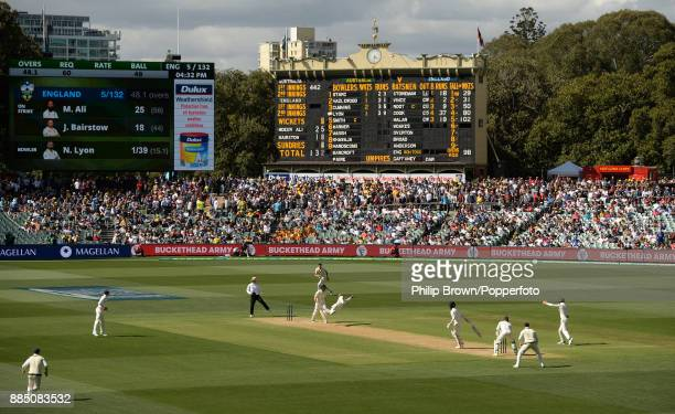 Nathan Lyon of Australia catches Moeen Ali of England off his own bowling during the third day of the second Ashes cricket test match between...