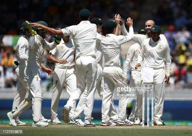 Nathan Lyon of Australia celebrates after taking the wicket of Chamika Karunaratne of Sri Lanka during day three of the Second Test match between...