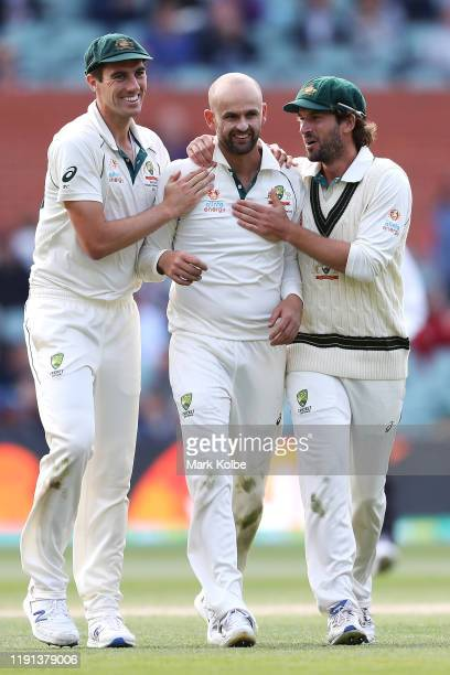 Nathan Lyon of Australia celebrates with his team mates Pat Cummins and Joe Burns of Australia after taking the wicket of Shaheen Shah Afridi of...