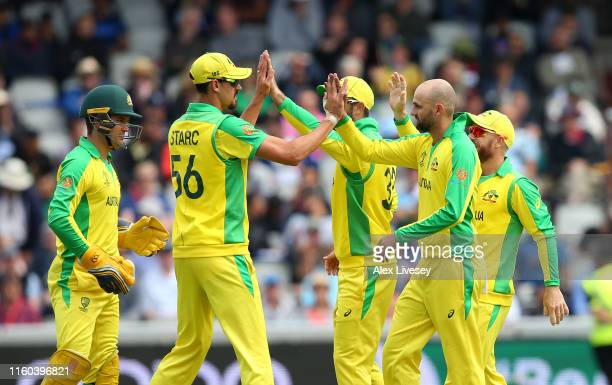 Nathan Lyon of Australia celebrates with Mitchell Starc and team mates after taking the wicket of Quinton De Kock of South Africa during the Group...