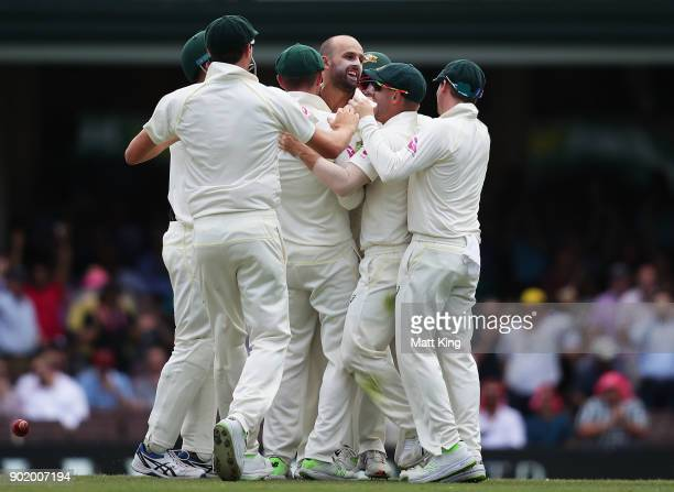 Nathan Lyon of Australia celebrates with team mates after taking the wicket of Alastair Cook of England during day four of the Fifth Test match in...