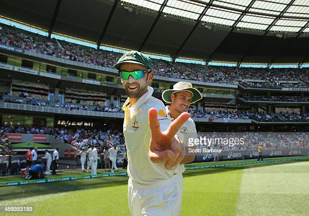 Nathan Lyon of Australia gestures as he walks out onto the field with Nathan CoulterNile of Australia after the tea break during day one of the...
