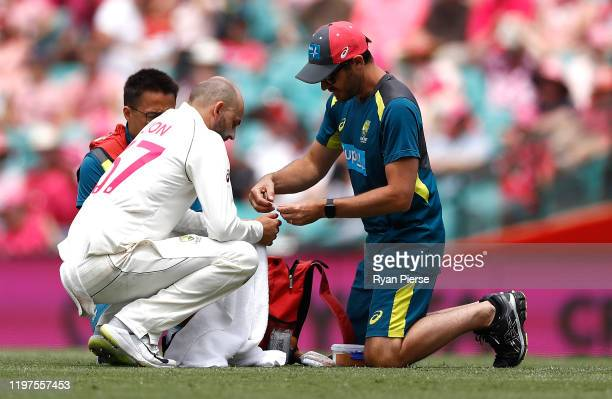 Nathan Lyon of Australia gets treatment from Australian Team Physiotherapist David Beakley after he injured his thumb while fielding off his own...