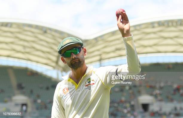 Nathan Lyon of Australia holds the ball up to the crowd after taking 6 wickets during day four of the First Test match in the series between...
