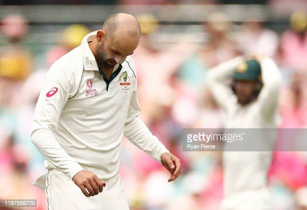 Nathan Lyon of Australia injures his thumb while fielding off his own bowling during day three of the Third Test match in the series between...