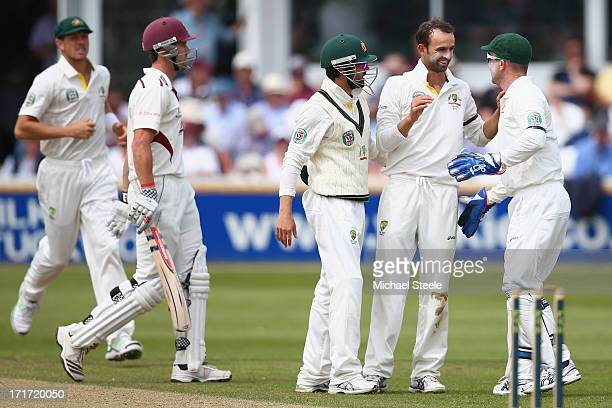 Nathan Lyon of Australia is congratulated by Brad Haddin and Ed Cowan after capturing the wicket of Nick Compton of Somerset during day three of the...