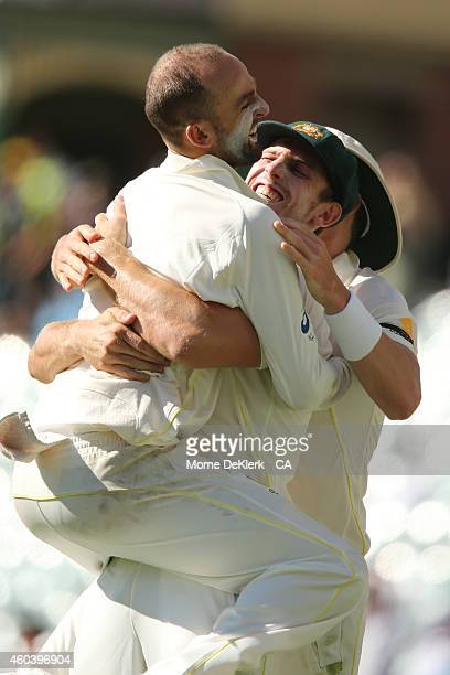 Nathan Lyon of Australia jumps onto teammate Mitch Marsh of Australia as they celebrate the wicket of Virat Kohli of India during day five of the...