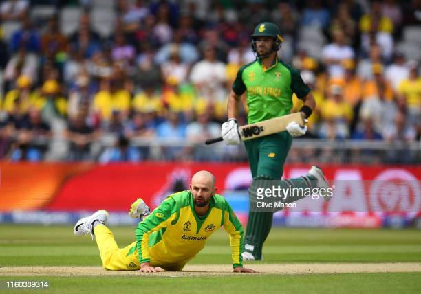 Nathan Lyon of Australia looks on as Quinton de Kock of South Africa and Aiden Markram of South Africa score during the Group Stage match of the ICC...