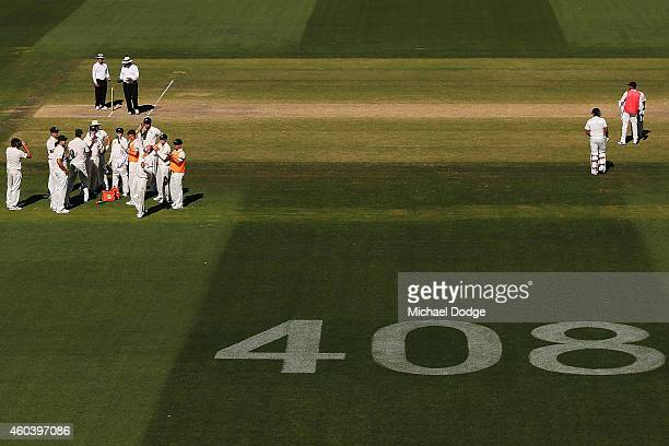 Nathan Lyon of Australia looks up to the sky as he celebrates his 5th wicket with teamates with the number 408 displayed dedicated to the late...